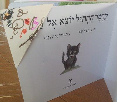 סימניה של יאיר הכין, מולבשת על אחד הספרים החביבים עליו לאחרונה - קרמר החתול יוצא אל היער, של מאיר שלו.