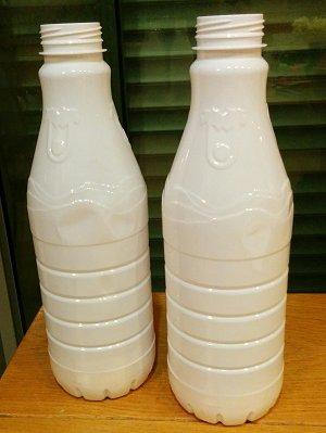 בקבוקי חלב מפלסטיק של יטבתה, מחכים ליצירה. - אחד לי ואחד ליאיר.